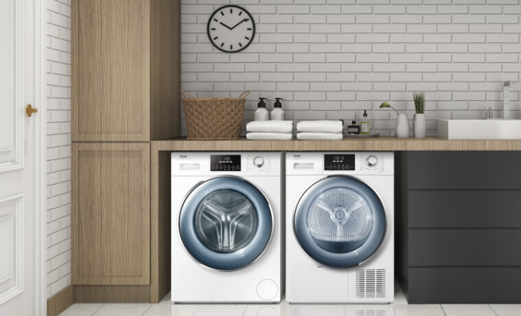 Stylish contemporary laundry with matching front load washing machine and dryer. Cabinets in dark grey and wood tones.