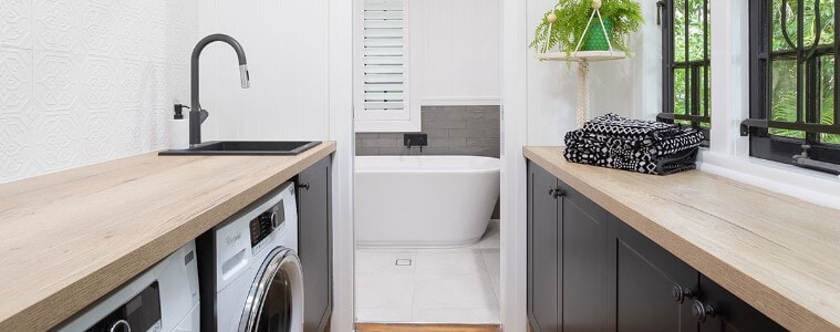 Classic styled galley laundry with white walls. Matching front load washer & dryer under wooden bench with charcoal cabinets.