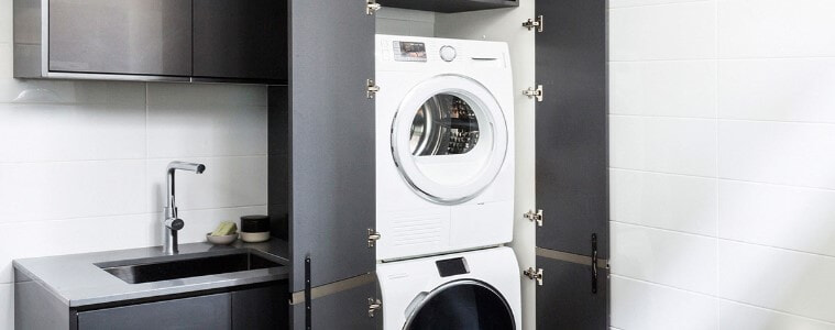 Small, compact laundry with stacked matching washing machine and dryer concealed behind dark grey cabinetry.