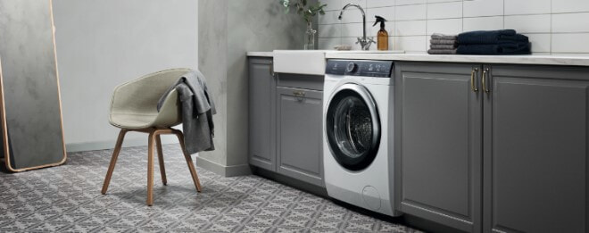 Laundry with patterned tile floor, granite benchtop, new washing machine, grey cabinetry and white subway tiled splashback.