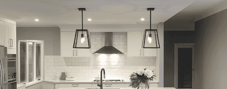 Contemporary styled black steel and glass pendant lights hanging in Hampton's style family kitchen   The Goode Guys