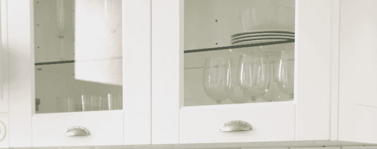 White shaker style cabinets with glass fronts and minimalist steel handles displaying wine glasses and white china   The Goode Guys